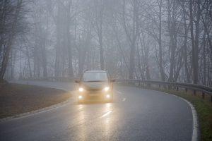 Voiture feux allumés dans le brouillard d'automneautorut
