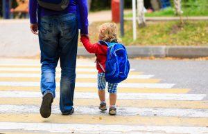 Un père et sa fille, petite, sur le chemin de l'école