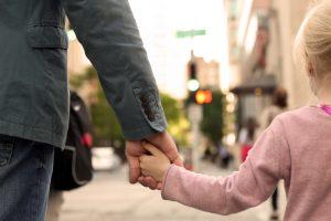 Une petite fille dinne la main à son père dans la rue