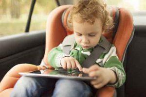Enfant en voiture jouant avec une tablette