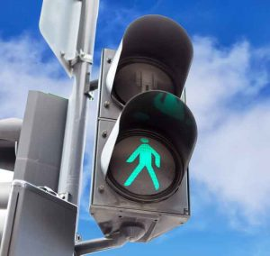 Traffic lights with the green light lit for pedestrians against blue sky background with clouds.