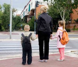 Woman holding hands of two kids representing traffic safety
