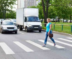 Woman crossing the street at pedestrian crossing